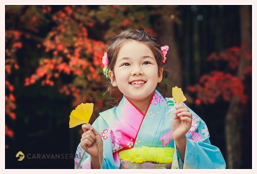 七五三 モミジを背景にイチョウの葉を持つ7才の女の子