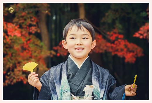 5歳の男の子の七五三 モミジを背景にイチョウの葉を持って