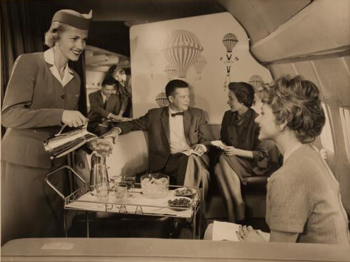 Glamorous Pan Am flight attendant serves coffee to passengers