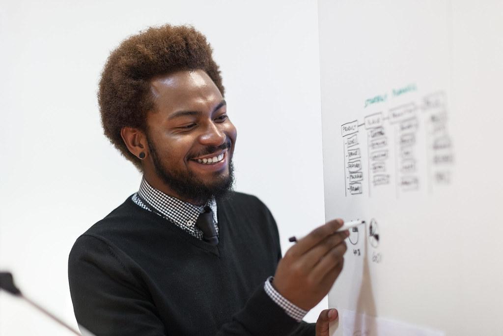 Man smiling holding pen to whiteboard