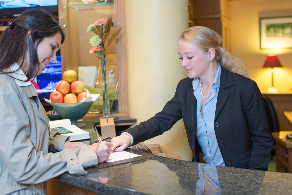 Woman checking in at front desk of hotel