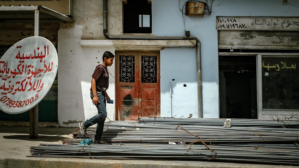 Young boy walking by a shop.