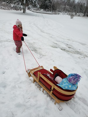 pulling little sister on the sled
