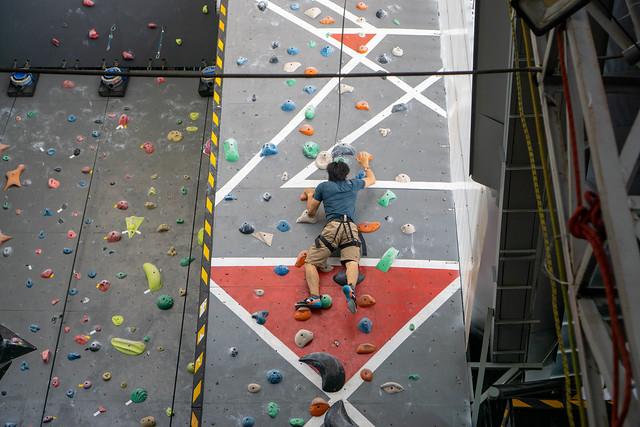 Person mit Sicherheitsgurt und Kletterschuhen klettert auf einer Wand mit Griffen in einer Indoor-Kletterhalle