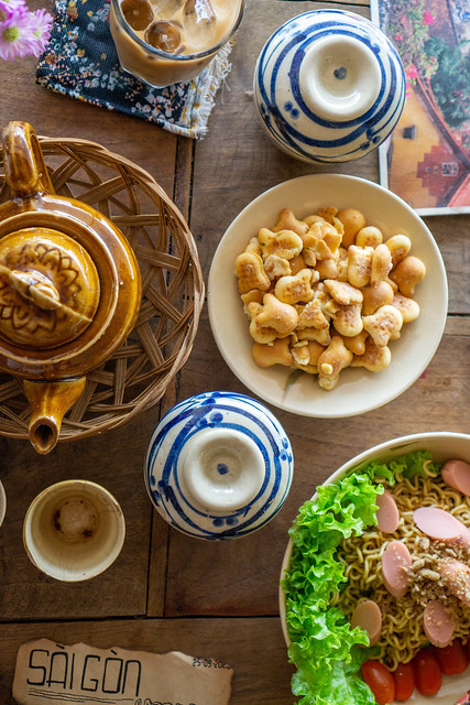 Top View Photo of Wooden Coffee Table with Ceramic Tea Pot, Cookies as Snack and Dried Noodles with Sausage and Lettuce
