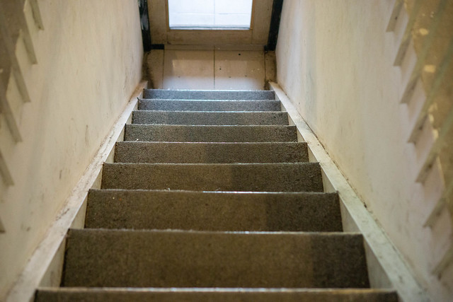 Stairs from first Floor to Ground Floor in an Old Building without Handrail leading to a Door