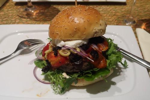 Burger mit selbstgebackenem Sesam-Bun, frisch angerührter Frischkäse-Chili-Creme, würzigem Tomaten-Basilikum-Sugo, Blattsalaten, gehackten Oliven, roter Zwiebel, geschmorten Tomaten, Mozzarella und Patties aus frisch gewolftem Rumpsteak (meiner)