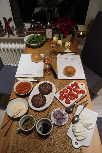 Burger mit selbstgebackenen Sesam-Buns, frisch angerührter Frischkäse-Chili-Creme, Tomaten-Basilikum-Sugo, Blattsalaten, gehackten Oliven, roter Zwiebel, geschmorten Tomaten, Mozzarella und Patties aus frisch gewolftem Rumpsteak