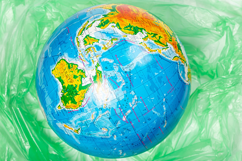 Model of the planet earth on the background of polyethylene plastic disposable trash bag, concept for pollution and environmental protection