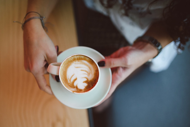 Young business woman holding cup of coffee from above.
