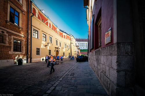 Tourists walking the historic Kanonicza Street with view of the Wawel Royal Castle, Krakow, Poland.  432-Edita