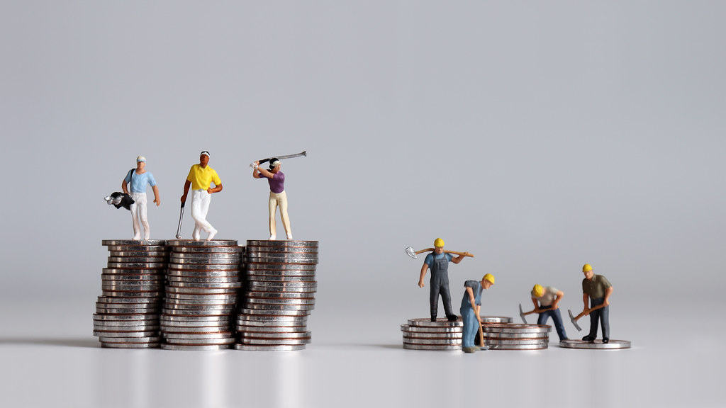 Plastic figurines standing on different sized stacks of coins