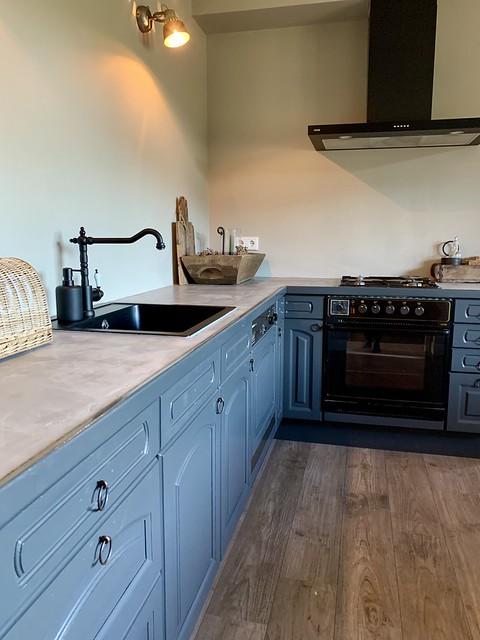 Landelijke blauwgrijze keuken zwarte kraan
