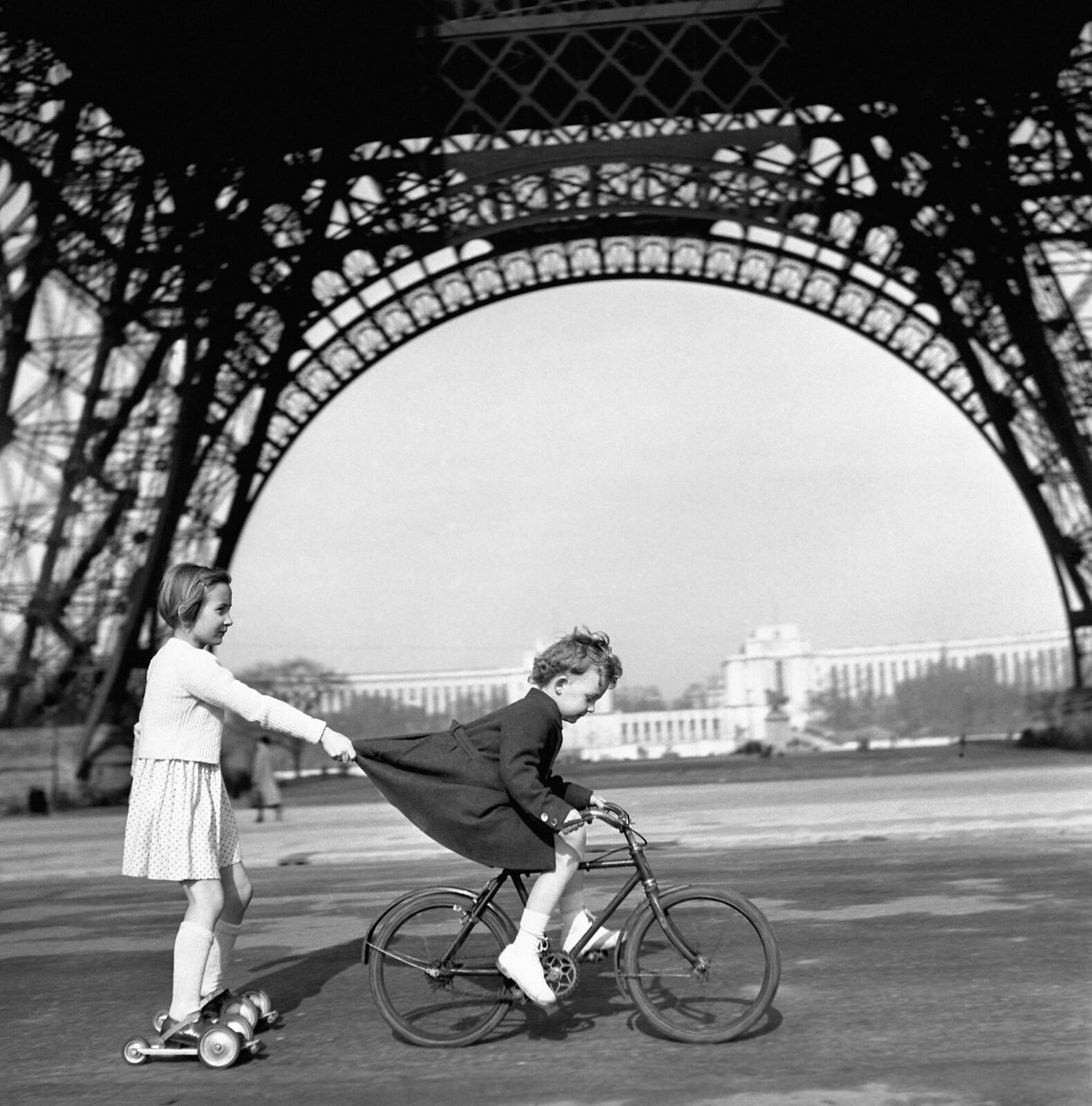 1943. Мальчик на велосипеде буксирует девочку на роликовых коньках под Эйфелевой башней на Марсовом поле