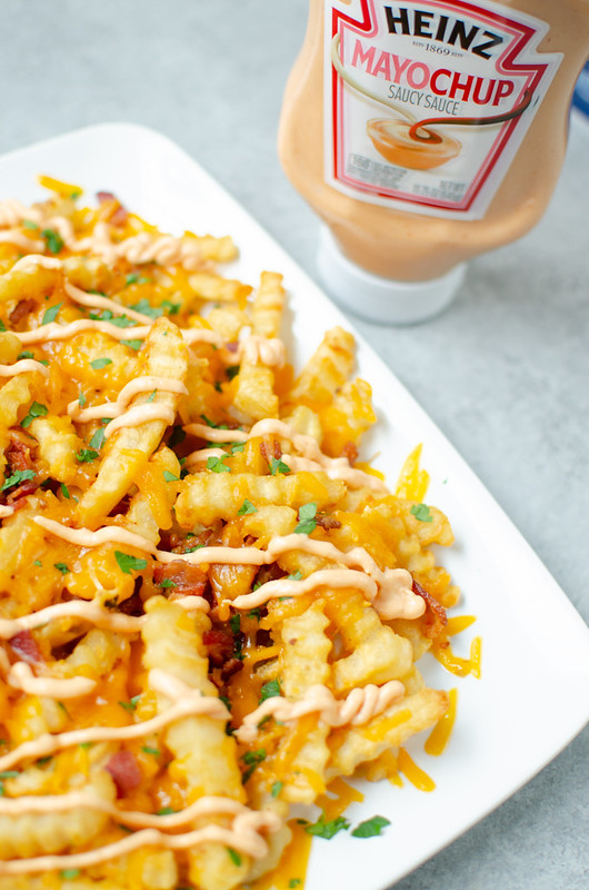 White plate of crinkle french fries topped with bacon, shredded cheddar cheese, chopped parsley, and mayochup; bottle of mayochup in background