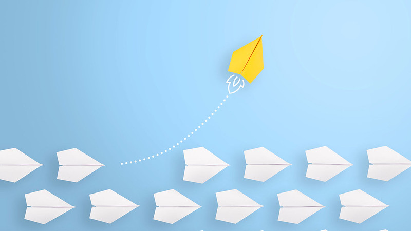 An arial photo of paper plans in a row with one plane in yellow taking a different course upwards to the others