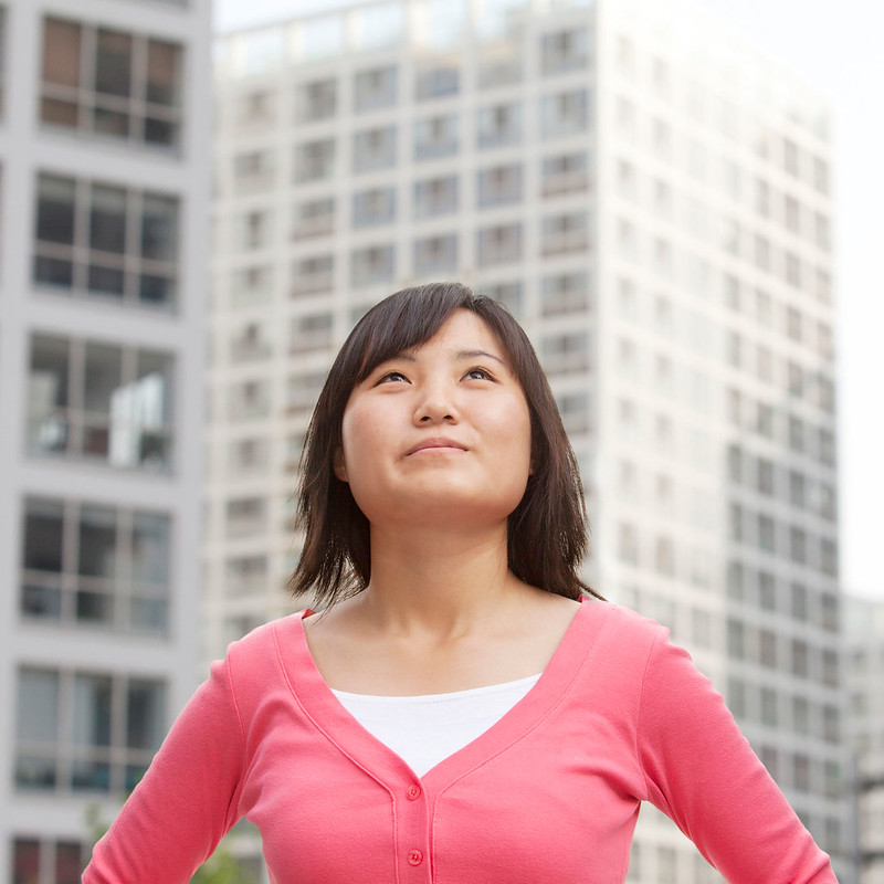 A woman standing outside some high rise buildings looking up at them