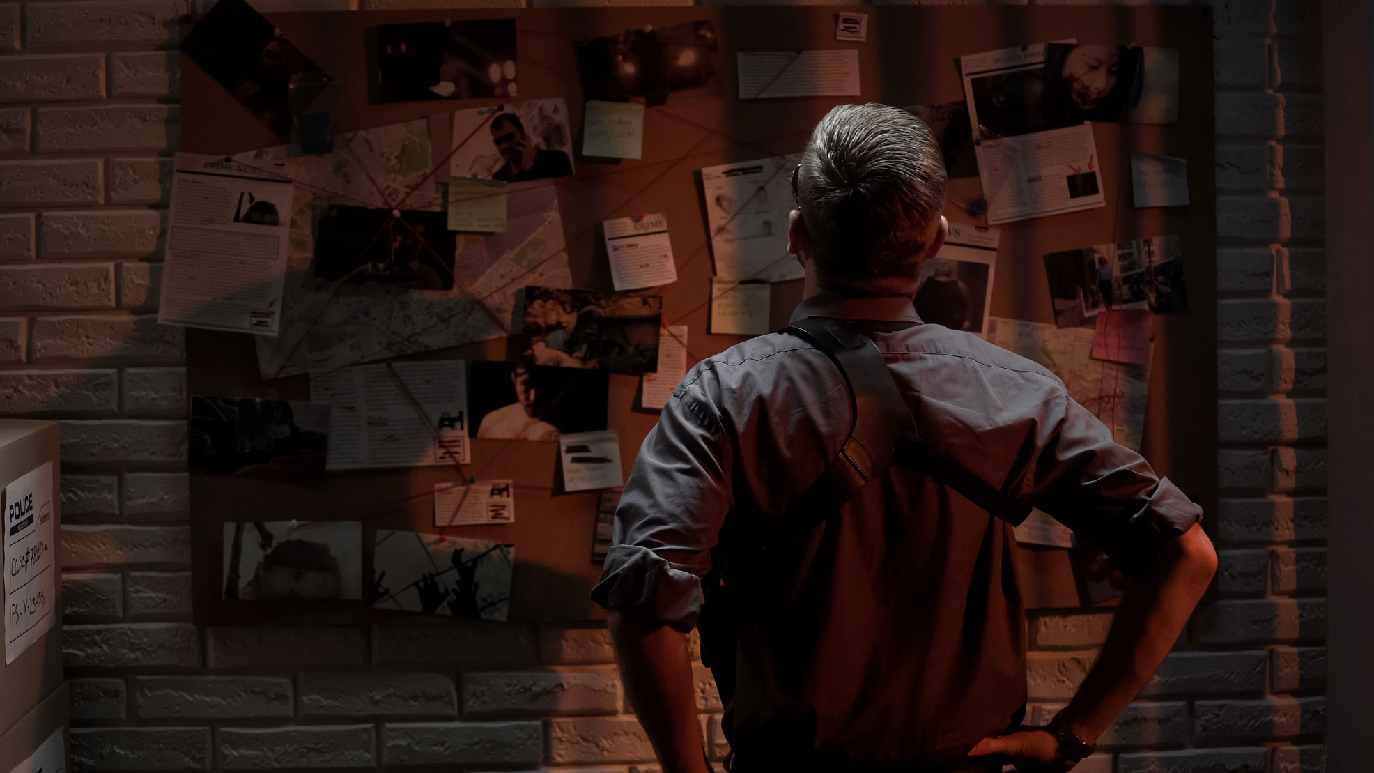 A police officer looking at a wall of evidence