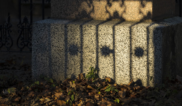Fence Shadows On a 100+ Years Old Stone Monument