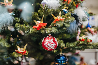 Red decorative ball with a snowflake and golden angels on a Christmas tree | by Ivan Radic