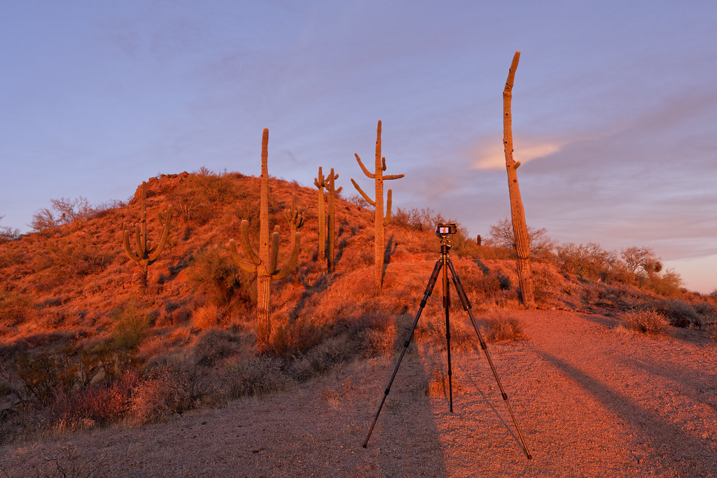 My Sony A6600 and tripod are bathed in the red light of sunset in front of the hill at George Doc Cavalliere Park in Scottsdale, Arizona on December 13, 2020. Original: _CAM7485.arw