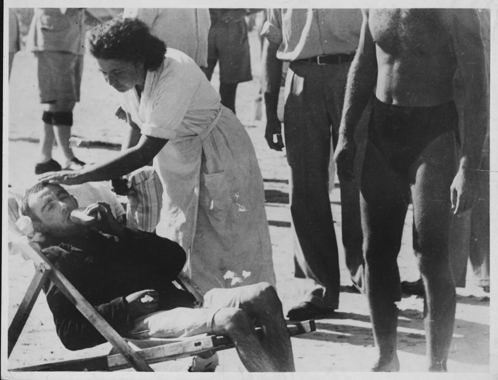 17. Женщина ухаживает за исхудавшим еврейским беженцем на пляже в Тель-Авиве