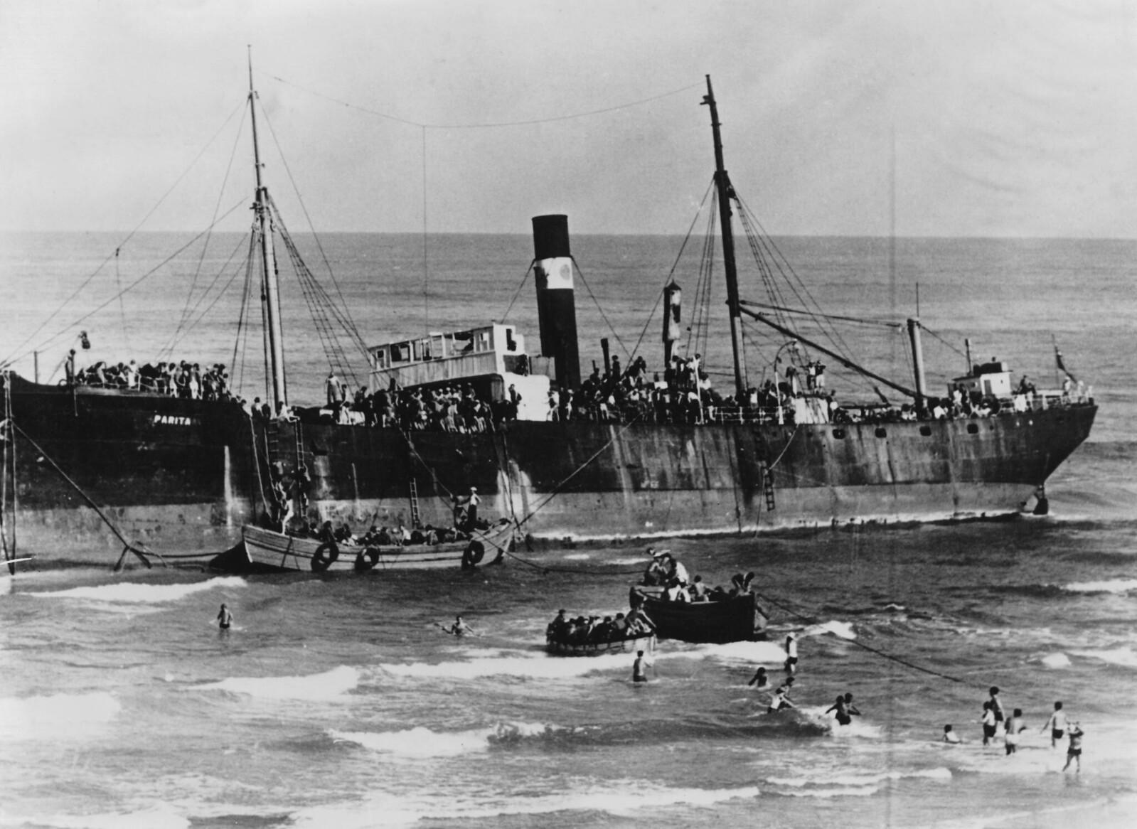 16. С помощью местных жителей около 800 еврейских беженцев начинают высадку с корабля SS Parita, стоящего на берегу моря в Тель-Авиве, Палестина, 22 августа