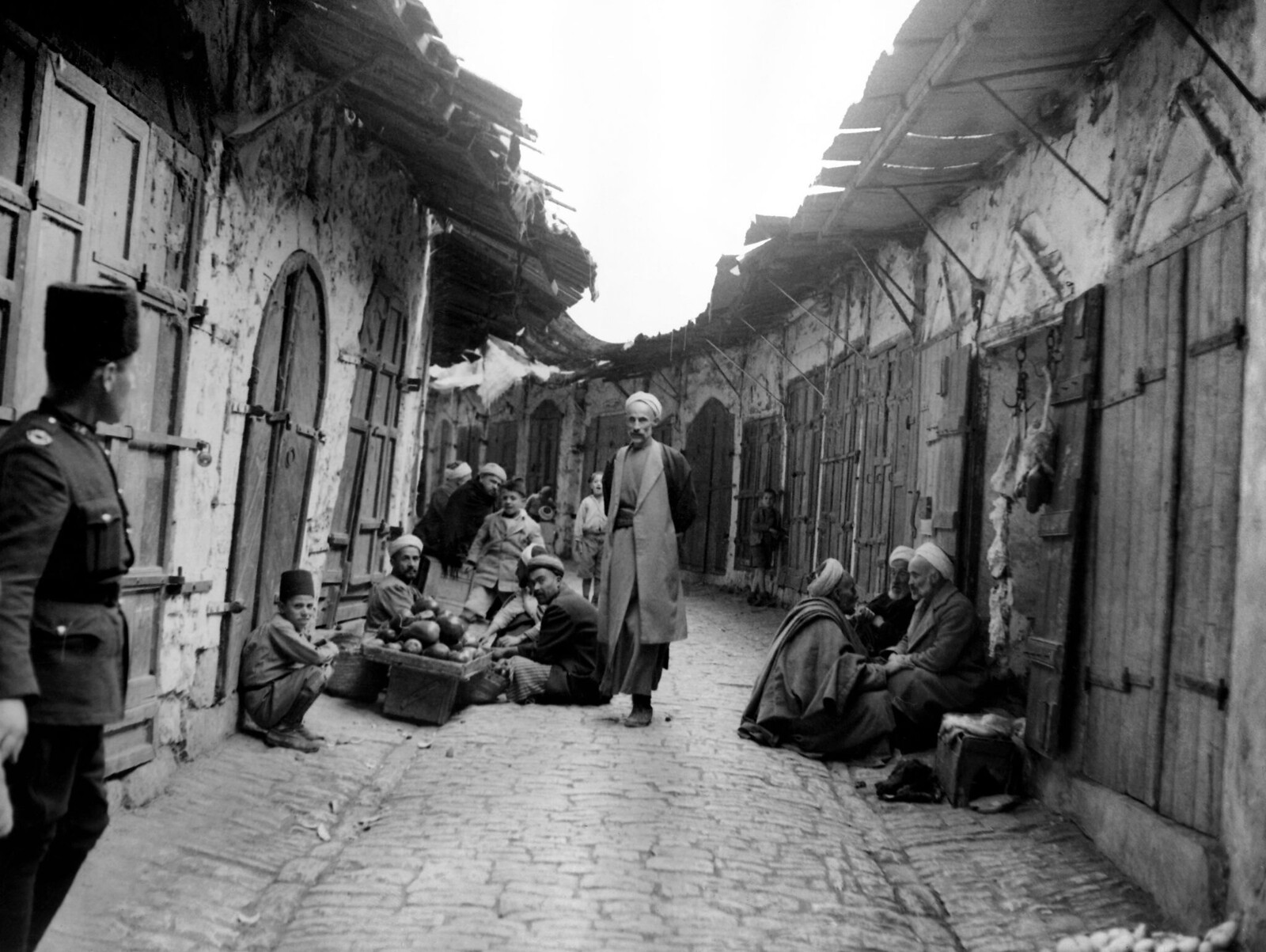 02. Арабы следят за полицейским на улице Хеврона, где магазины закрыты из-за забастовки во время арабского восстания