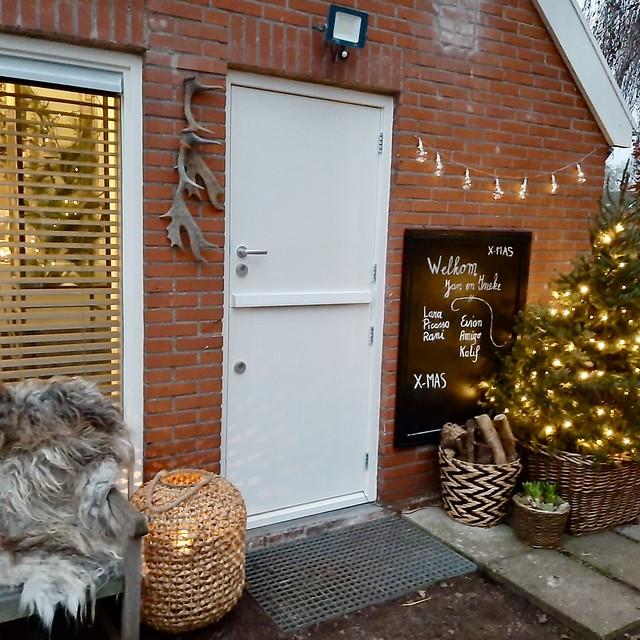 Kerstversiering buiten kerstkrans achterdeur