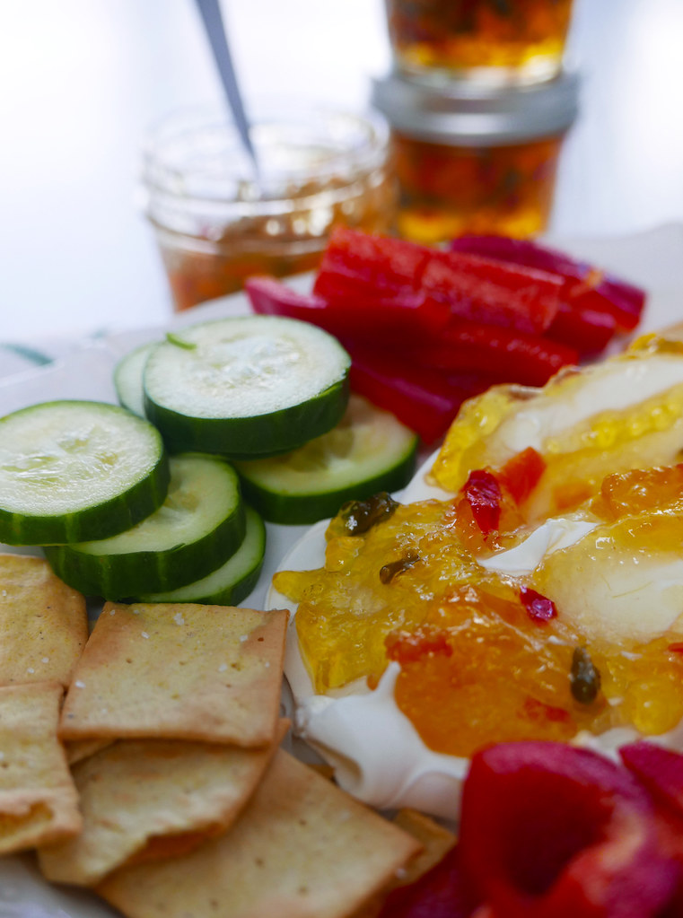 A Platter Prepared With Hot Pepper Jelly, Cream Cheese, Crackers, Bell Peppers, and Cucumbers.