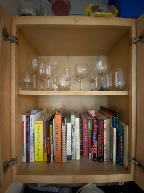 Glassware and recipe books in a glass-fronted cabinet, with books on the bottom where they belong