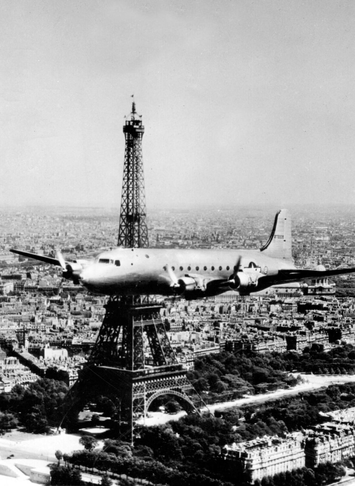 1945. Серебристый самолет C-54 Skymaster ВВС США пролетает мимо Эйфелевой башни, июнь