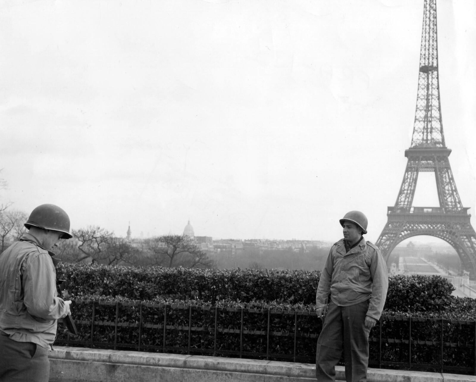 1945. Приехав прямо из Аахена, два американских солдата получив 72-часовую увольнительную, фотографируют друг друга перед Эйфелевой башней