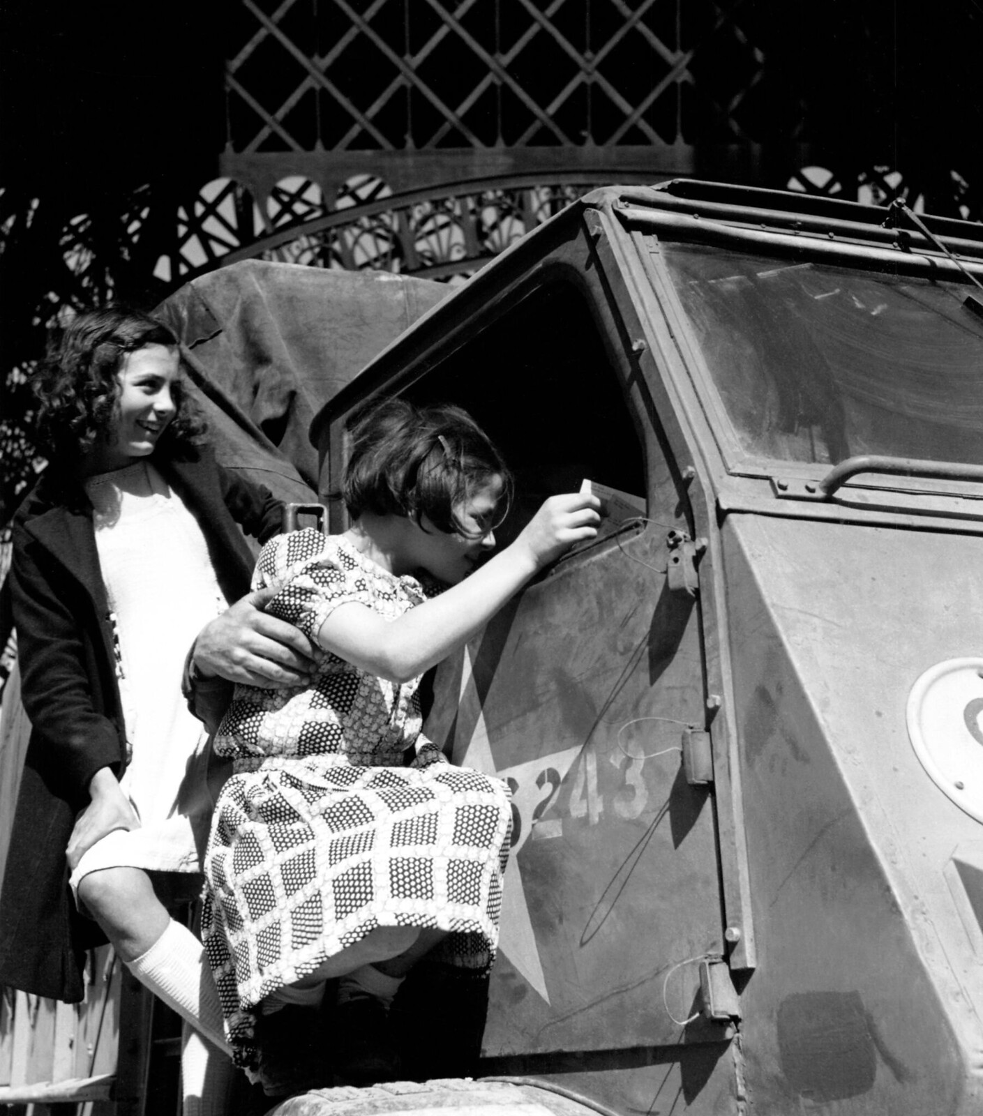 1944. Девочки разглядывают грузовики с американскими солдатами под Эйфелевой башней, 27 августа