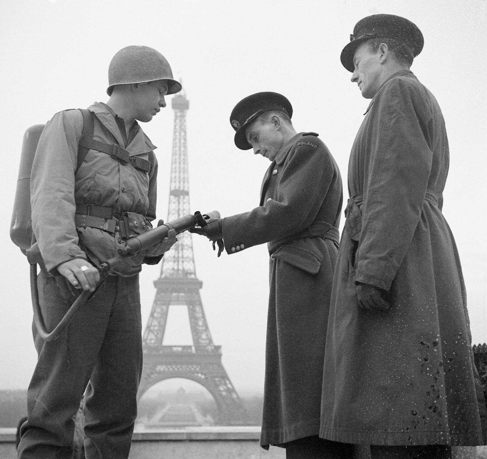 1944. Американский солдат показывает двум офицерам польской армии свой огнемет, когда они отдыхают возле Эйфелевой башни