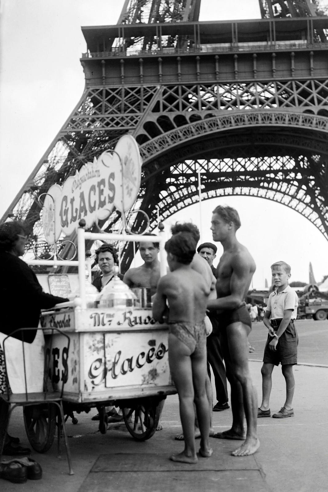 1945. Молодые люди в купальных костюмах покупают мороженое возле Эйфелевой башни в июле
