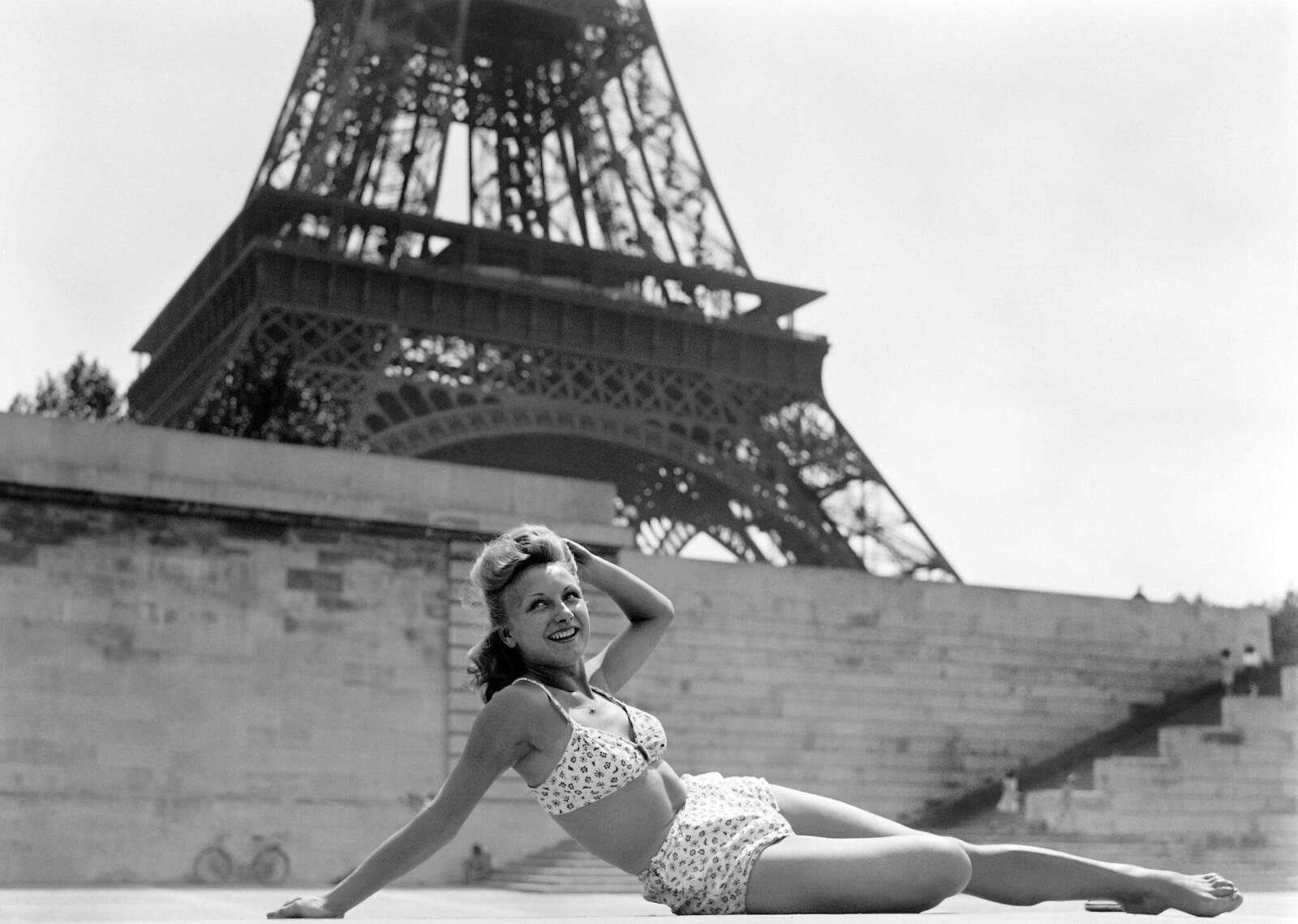 1944. Женщина загорает на берегу Сены возле Эйфелевой башни. Август