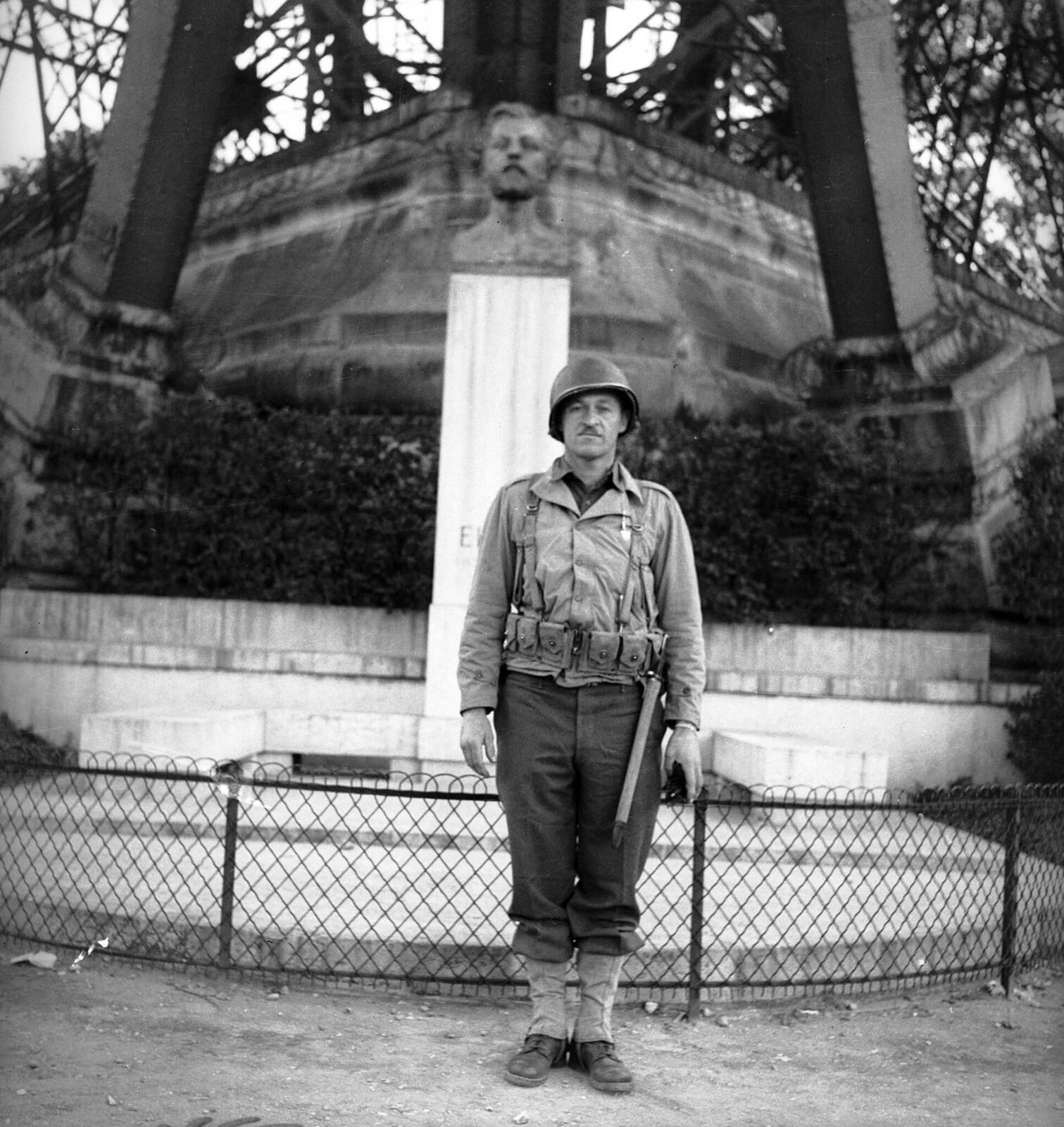1944.  Американский солдат позирует у подножия Эйфелевой башни. Париж, август