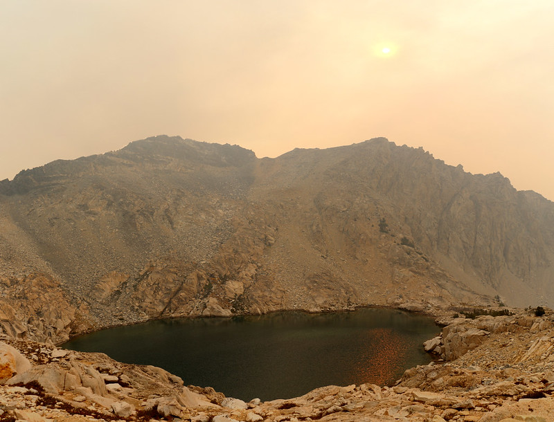 Smoky orange sun and orange reflections on the lake just south of Glen Pass on the Pacific Crest Trail