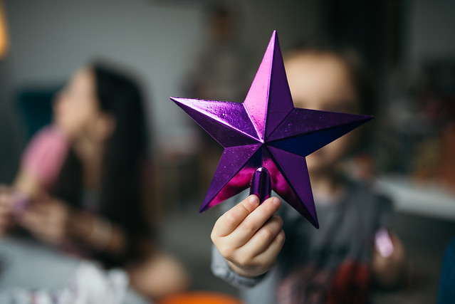 Little girl holding purple star.