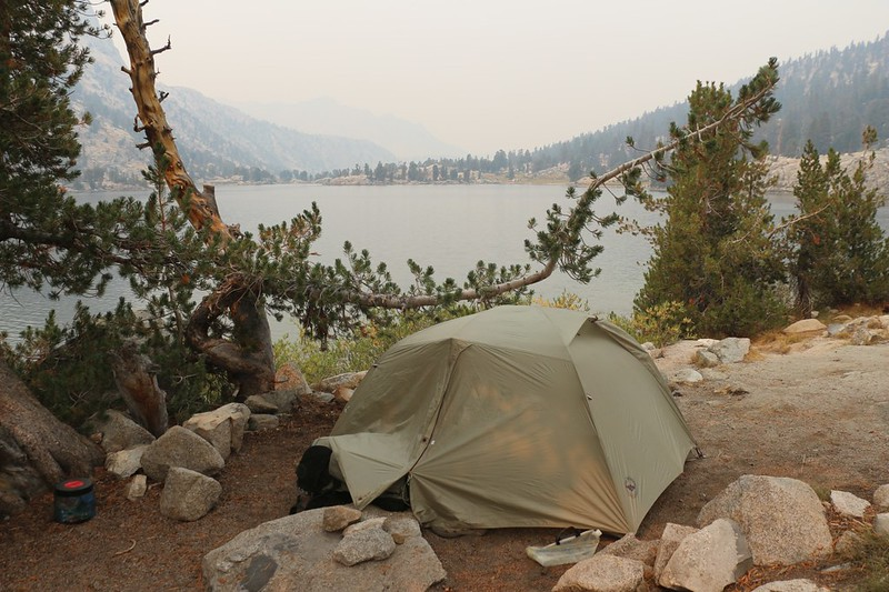 Our campsite on Lower Rae Lake with orange sunlight filtering down through a tree onto the tent