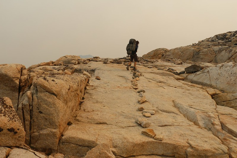 The gray granite turned orange thanks to the smoky sky on the Pacific Crest Trail north of Glen Pass