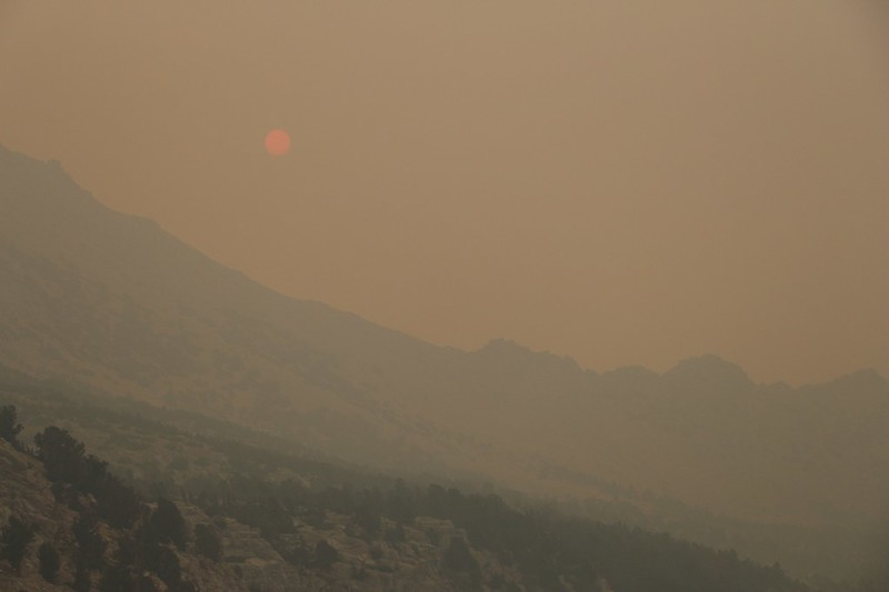 An orange sun rises into the smoky air above Kearsarge Pass, from the trail above Bullfrog Lake