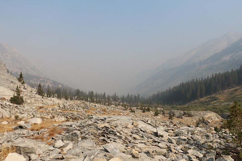 Looking north on the PCT, down into the hazy valley below Dollar Lake, where the South Fork of Woods Creek flows