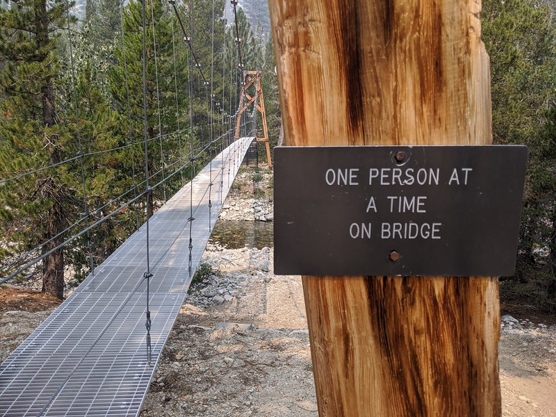 The sign warns us that only one person should cross the suspension bridge at one time