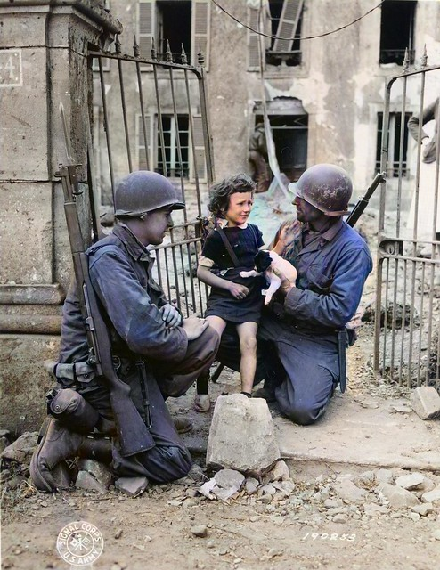 American Soldiers take time out to comfort a little French Girl as U.S. Troops forge ahead in France_colorSAI_result