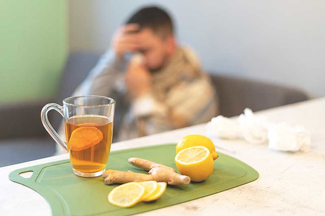 The concept of the disease, winter time. Black tea, lemon and ginger on the table, a sick man in the background, flu. Epidemic, sick leave, temperature, stress
