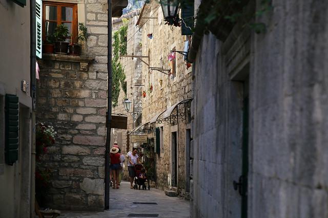 A narrow alleyway twisted between medieval sandstone buildings