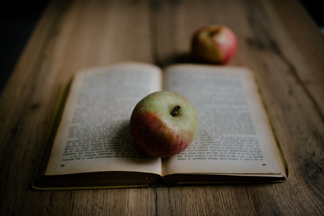 Apple on old book closeup.