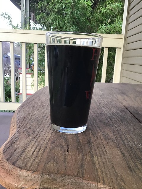 Breakside stout in glass, on table outdoors.